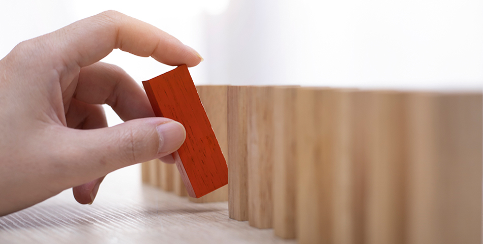 Person placing a red, wooden block - Customer Communications: Removing the Risk