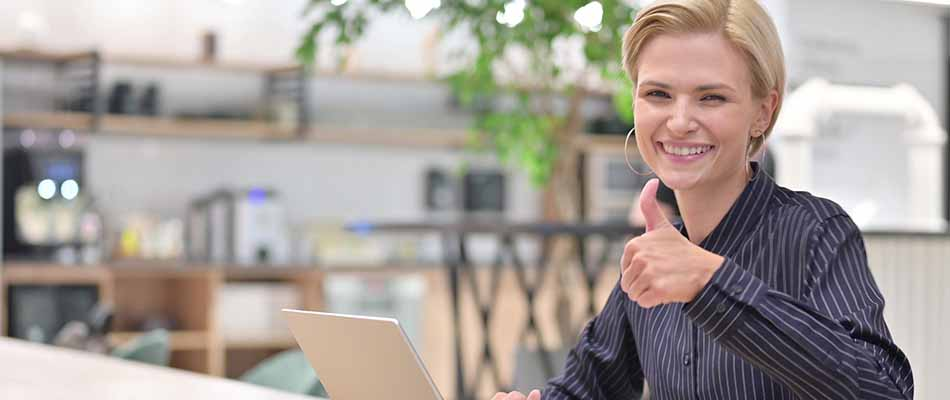 Woman using laptop giving thumbs-up