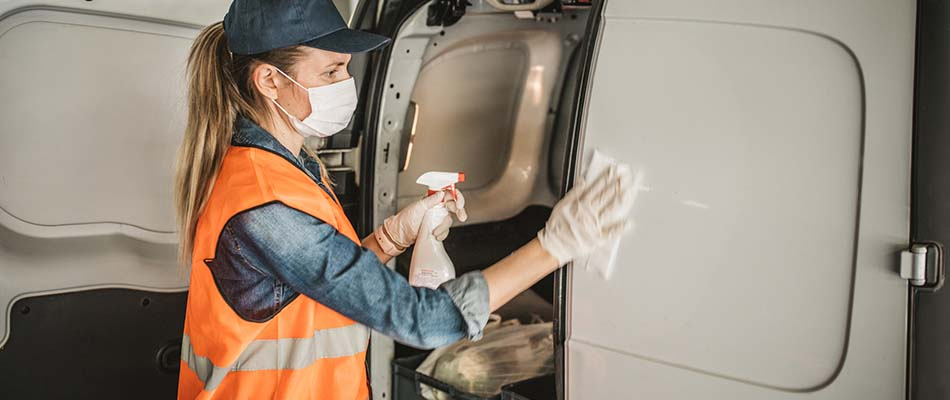 Woman wipes down vehicle - Workplace Changes: Prepping for the New Normal